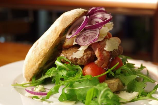 Domácí burger s rukolou, rajčátky a parmezánem v rustikální housce